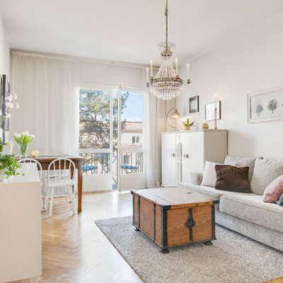 Mid-sized danish open concept and formal medium tone wood floor living room photo in Stockholm with white walls and a wall-mounted tv