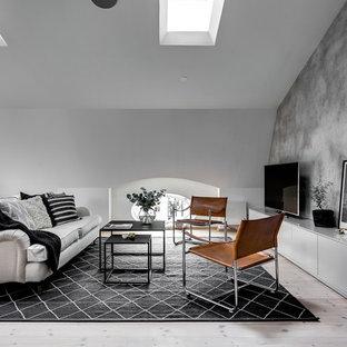 Inredning av ett skandinaviskt stort allrum med öppen planlösning, med grå väggar, ljust trägolv och en fristående TV