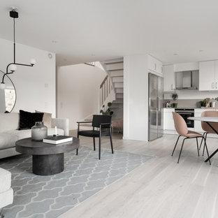 Foto på ett mellanstort minimalistiskt allrum med öppen planlösning, med vita väggar, ljust trägolv och beiget golv