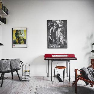 Inredning av ett nordiskt vardagsrum, med ett musikrum, vita väggar, ljust trägolv och beiget golv