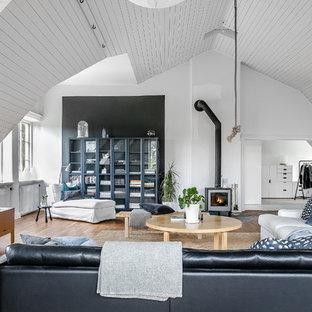 Foto på ett skandinaviskt allrum med öppen planlösning, med vita väggar, ljust trägolv, en öppen vedspis, en spiselkrans i metall och en fristående TV