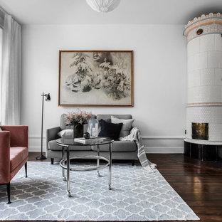 Inredning av ett skandinaviskt vardagsrum, med vita väggar, mörkt trägolv, en öppen hörnspis och brunt golv