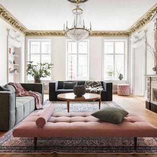 Skandinavisk inredning av ett separat vardagsrum, med ett finrum, vita väggar, mellanmörkt trägolv och en standard öppen spis