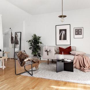 Inredning av ett skandinaviskt litet allrum med öppen planlösning, med vita väggar och ljust trägolv