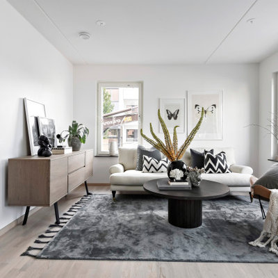 Danish formal light wood floor and beige floor living room photo in Stockholm with white walls, no fireplace and no tv