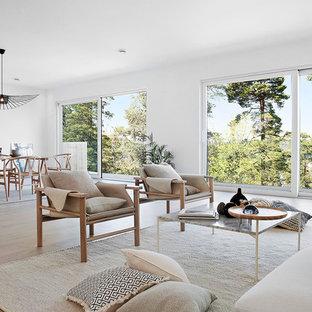 Exempel på ett stort modernt allrum med öppen planlösning, med vita väggar, ljust trägolv och beiget golv