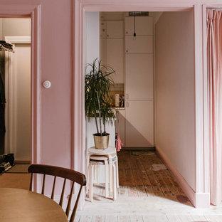 Foto di un piccolo soggiorno nordico aperto con pareti rosa e pavimento in legno massello medio