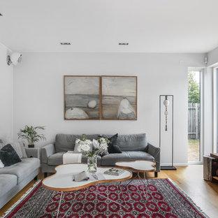 Foto på ett funkis vardagsrum, med vita väggar, mellanmörkt trägolv, en väggmonterad TV och brunt golv