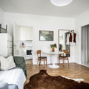 Foto på ett litet skandinaviskt allrum med öppen planlösning, med vita väggar, mellanmörkt trägolv, en väggmonterad TV och brunt golv