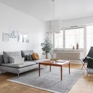 Foto på ett nordiskt vardagsrum, med vita väggar, mellanmörkt trägolv och brunt golv