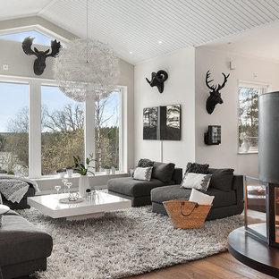 Modelo de salón para visitas abierto, escandinavo, de tamaño medio, con paredes blancas, suelo de madera oscura y chimenea de esquina