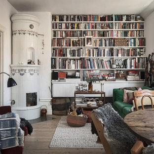 Inredning av ett eklektiskt litet allrum med öppen planlösning, med ett bibliotek, vita väggar, ljust trägolv, en öppen vedspis och en spiselkrans i trä