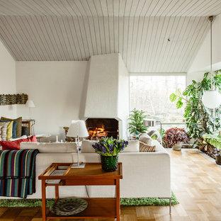 Inspiration för ett stort 50 tals vardagsrum, med vita väggar, mellanmörkt trägolv, en spiselkrans i gips, beiget golv och en standard öppen spis