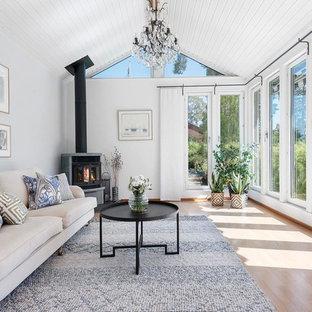 Inredning av ett klassiskt separat vardagsrum, med grå väggar, ljust trägolv, en öppen vedspis och brunt golv