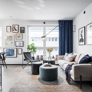 Foto på ett stort skandinaviskt allrum med öppen planlösning, med vita väggar, ljust trägolv och grått golv