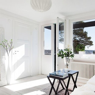 Medium sized scandinavian formal enclosed living room in Stockholm with white walls, painted wood flooring, no fireplace and no tv.