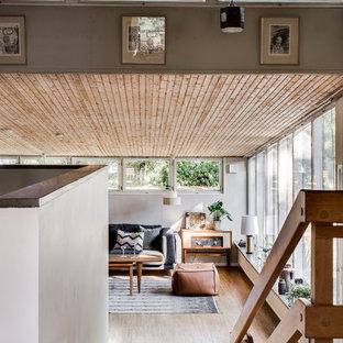 Foto på ett stort retro allrum med öppen planlösning, med vita väggar och mellanmörkt trägolv