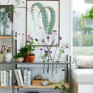 Minimalistisk inredning av ett vardagsrum, med vita väggar, ljust trägolv och beiget golv