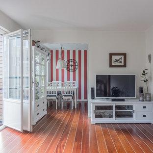 ストックホルムの小さい北欧スタイルのおしゃれなLDK (ラミネートの床、据え置き型テレビ、オレンジの床) の写真
