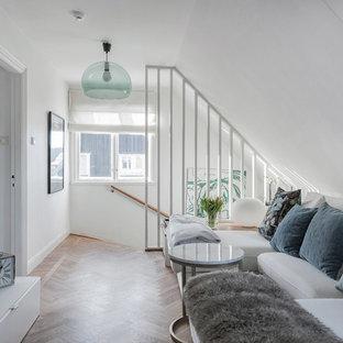 Idéer för att renovera ett litet skandinaviskt loftrum, med vita väggar, mellanmörkt trägolv, en väggmonterad TV och brunt golv