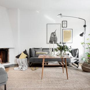 Inredning av ett nordiskt mellanstort vardagsrum, med vita väggar, mellanmörkt trägolv, en öppen hörnspis, en spiselkrans i betong, ett finrum och brunt golv