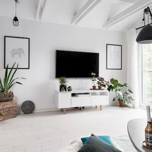 Bild på ett mellanstort nordiskt loftrum, med vita väggar, ljust trägolv och en väggmonterad TV