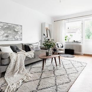 Inspiration för mellanstora minimalistiska allrum med öppen planlösning, med vita väggar, mellanmörkt trägolv, en fristående TV och brunt golv