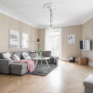 Nordisk inredning av ett mellanstort vardagsrum, med beige väggar, beiget golv, ljust trägolv och en väggmonterad TV