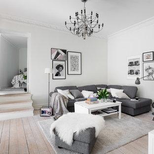 Idéer för att renovera ett mellanstort minimalistiskt vardagsrum, med vita väggar, ljust trägolv, beiget golv och ett bibliotek