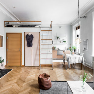 Inspiration for a small scandinavian open concept medium tone wood floor living room remodel in Gothenburg with white walls