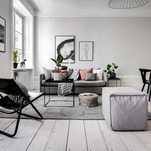 Idéer för att renovera ett mellanstort nordiskt allrum med öppen planlösning, med grå väggar, ljust trägolv, beiget golv och ett finrum