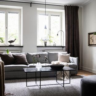 Idéer för att renovera ett funkis vardagsrum, med grå väggar, mellanmörkt trägolv och brunt golv
