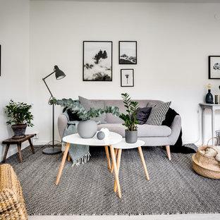 Exempel på ett nordiskt allrum med öppen planlösning, med vita väggar, grått golv och ljust trägolv