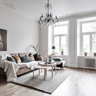 Inredning av ett nordiskt stort separat vardagsrum, med vita väggar, ljust trägolv och beiget golv
