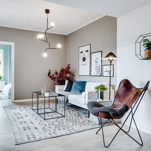 Idéer för att renovera ett mellanstort nordiskt allrum med öppen planlösning, med beige väggar, ljust trägolv och grått golv