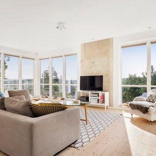 Ejemplo de salón para visitas abierto, nórdico, grande, sin chimenea, con paredes blancas, suelo de madera clara y televisor independiente
