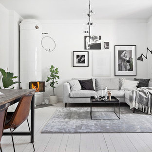Design ideas for a scandinavian living room in Stockholm with white walls, painted wood flooring, a corner fireplace, a tiled fireplace surround and white floors.