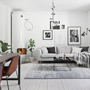 Inredning av ett minimalistiskt vardagsrum, med vita väggar, målat trägolv, en öppen hörnspis, en spiselkrans i trä och vitt golv
