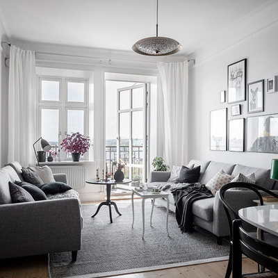 Inspiration for a scandinavian formal and open concept light wood floor and beige floor living room remodel in Gothenburg with white walls