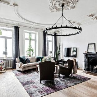 Foto på ett stort vintage vardagsrum, med vita väggar, ljust trägolv, en standard öppen spis, en spiselkrans i sten, en väggmonterad TV och beiget golv