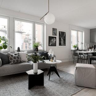Inspiration för mellanstora nordiska allrum med öppen planlösning, med vita väggar, ljust trägolv och beiget golv