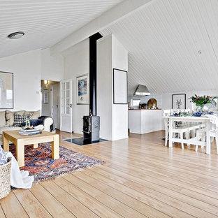 Idéer för att renovera ett lantligt allrum med öppen planlösning, med vita väggar, ljust trägolv, en öppen vedspis, en spiselkrans i metall och beiget golv