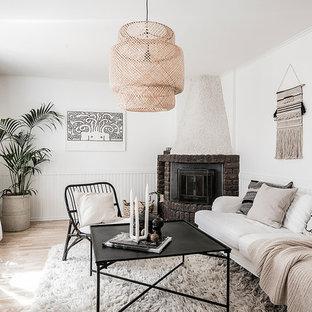 Inredning av ett nordiskt separat vardagsrum, med vita väggar, ljust trägolv, en öppen hörnspis, en spiselkrans i tegelsten och beiget golv