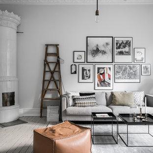 Inspiration för mellanstora skandinaviska separata vardagsrum, med ljust trägolv, en spiselkrans i trä, grå väggar, en öppen vedspis och grått golv