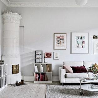 Klassisk inredning av ett mellanstort separat vardagsrum, med ljust trägolv, en öppen vedspis, en spiselkrans i trä, grå väggar och beiget golv