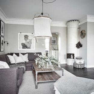 Inspiration för ett skandinaviskt separat vardagsrum, med beige väggar, mörkt trägolv, en öppen hörnspis, en spiselkrans i metall och svart golv