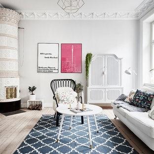 Inspiration för ett mellanstort skandinaviskt separat vardagsrum, med ljust trägolv, en öppen hörnspis, en spiselkrans i trä, beiget golv och grå väggar