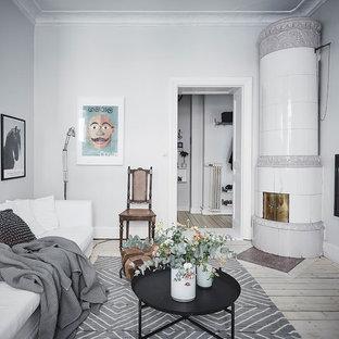 Foto på ett minimalistiskt separat vardagsrum, med vita väggar, ljust trägolv, en öppen hörnspis, en spiselkrans i metall, en väggmonterad TV och beiget golv