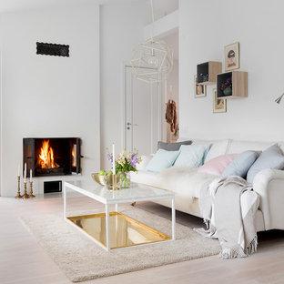 Exempel på ett mellanstort nordiskt allrum med öppen planlösning, med vita väggar, ljust trägolv, en standard öppen spis och en spiselkrans i gips