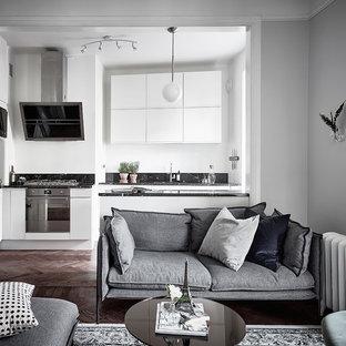 Inspiration för nordiska vardagsrum, med grå väggar och mörkt trägolv